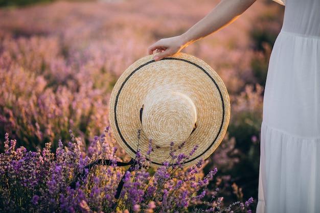 Женщина держит шляпу в поле лаванды крупным планом Бесплатные Фотографии