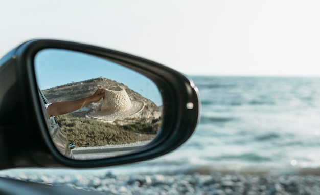 Woman holding hat out of window in car mirror view Free Photo