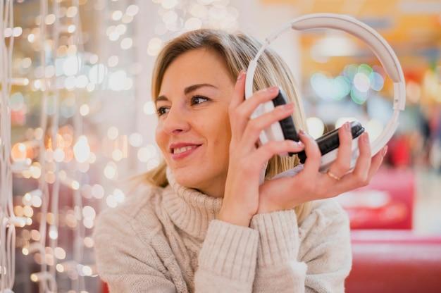 クリスマスライトを見てヘッドフォンを保持している女性 無料写真