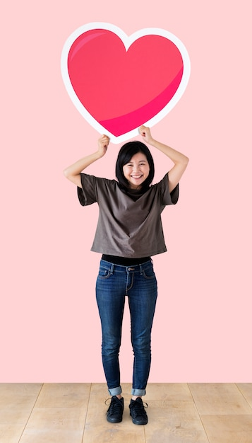 Woman holding a heart emoticon in a studio Free Photo