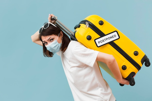 Woman holding her baggage for a cancelled event Premium Photo