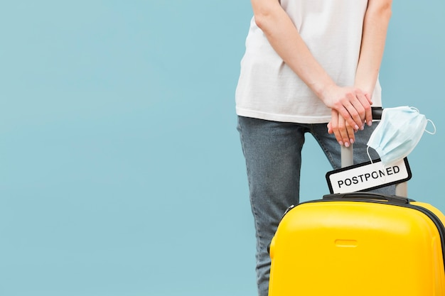 Woman holding her baggage with a postponed sign with copy space Premium Photo