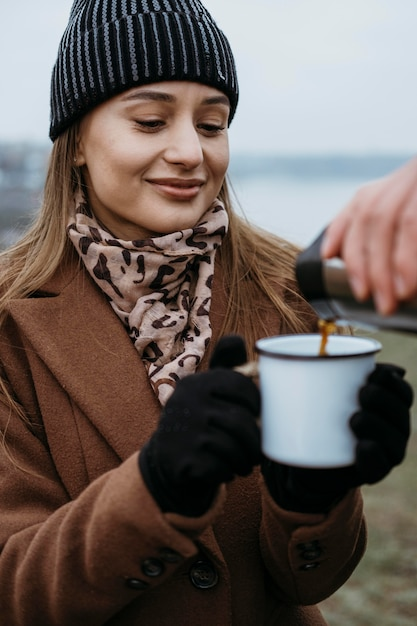 屋外で温かい飲み物を飲むために彼女のカップを保持している女性 無料写真