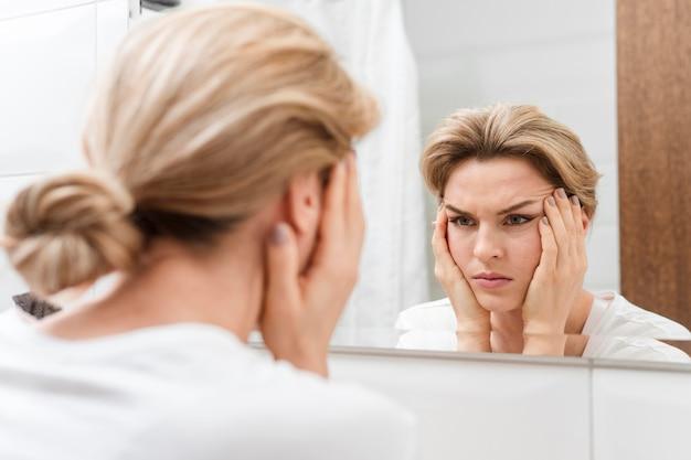 Donna che tiene il suo viso e guardarsi allo specchio Foto Gratuite