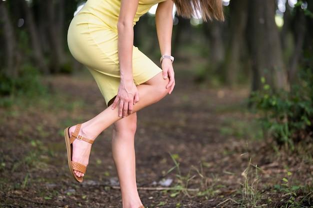 Женщина, держащая ее колено руками, болит в суставах. Premium Фотографии