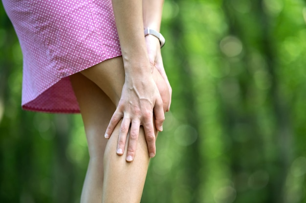Женщина, держащая ее колено руками. Premium Фотографии