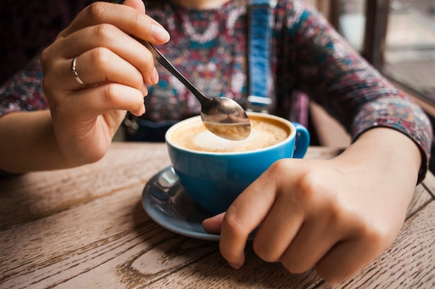Woman holding hot cup of coffee at restaurant Free Photo