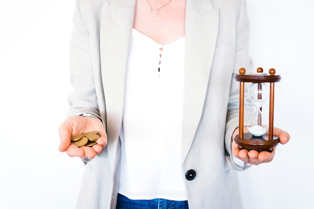 Woman holding hourglass and coins isolated on white background. time investment and retirement saving. urgency countdown timer for business deadline concept. time is money Premium Photo