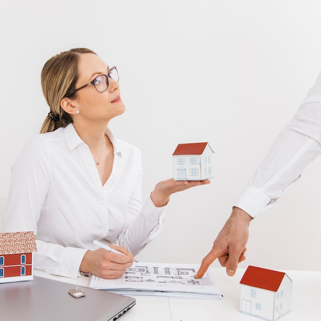 Woman holding house model looking at her colleague pointing on blue print over desk Free Photo