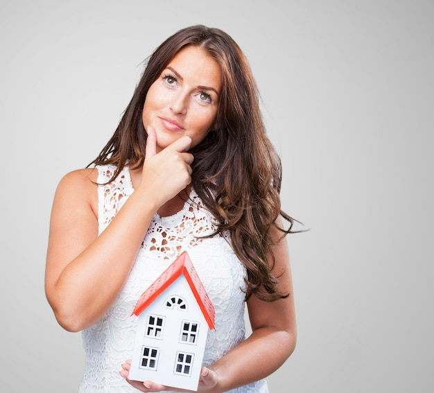 Woman holding a house and thinking about something Free Photo