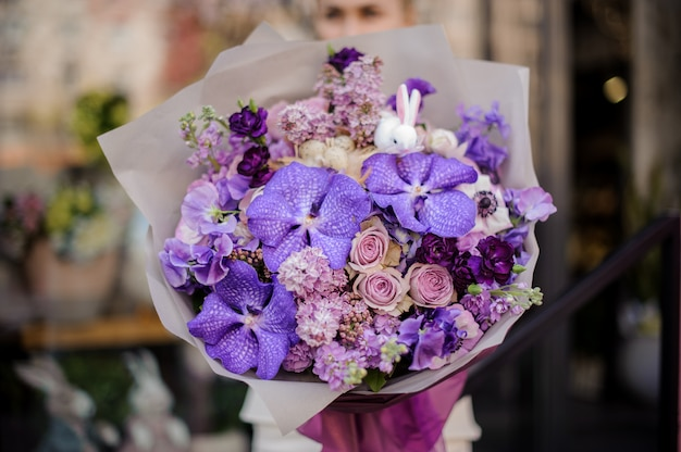 Woman holding a huge bouquet of tender violet color flowers Premium Photo