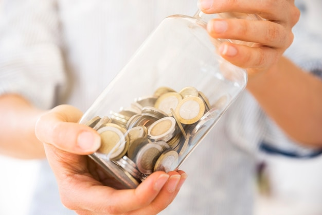 Woman holding a jar with money Free Photo