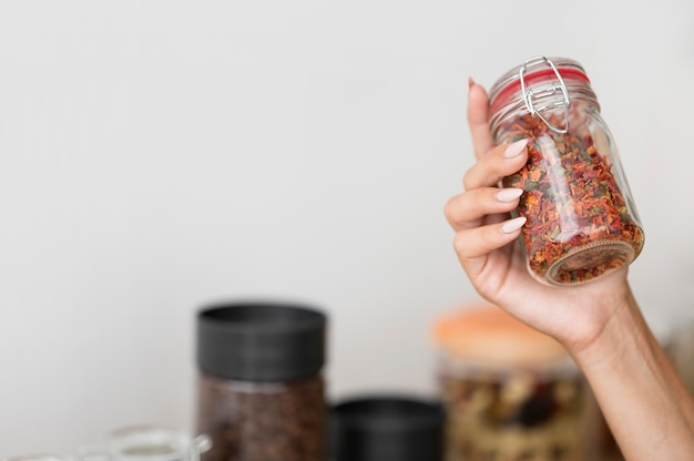 Woman holding a jar with spices with copy space Free Photo