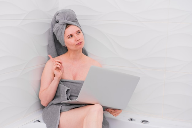 Woman holding a laptop in the bathroom Free Photo