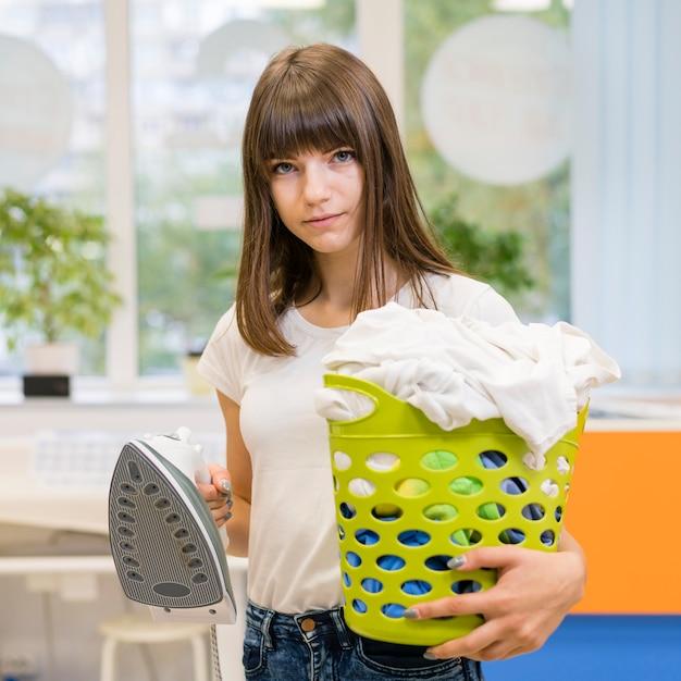 Woman holding laundry basket medium shot Free Photo