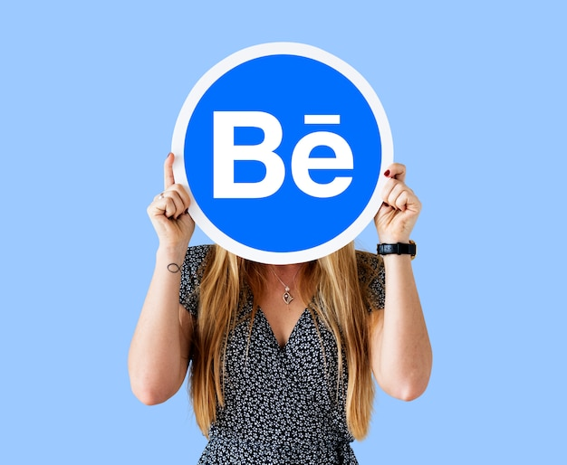 Woman holding a logo of behance Free Photo