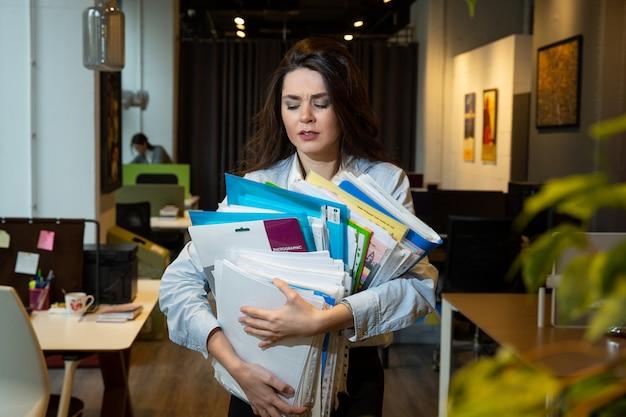 Женщина держит много папок Бесплатные Фотографии