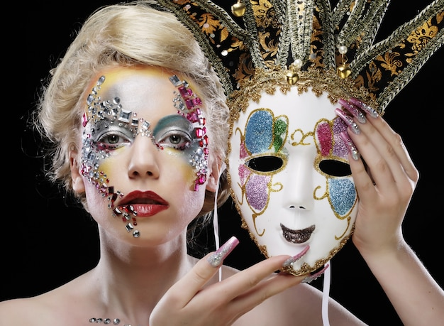 Woman holding a mask with artistic make up Premium Photo