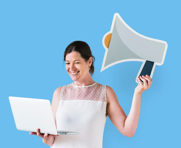Woman holding a megaphone icon and using a laptop Free Photo