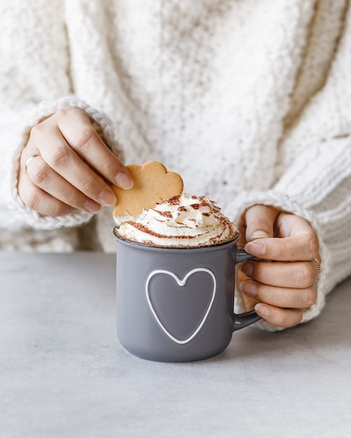Woman holding metal grey mug of hot chocolate with whipped cream and cookie in hands. Premium Photo