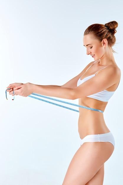 Metro della tenuta della donna che misura forma perfetta del suo bello corpo Foto Gratuite
