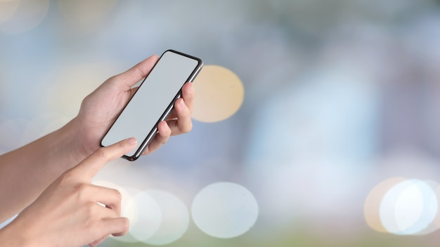 Woman holding mobile phone and showing blank screen for graphic montage Premium Photo