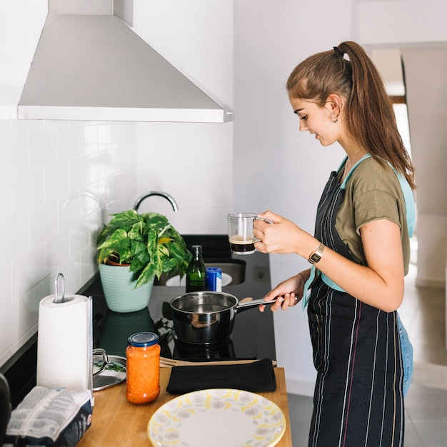 Woman holding mug of coffee preparing food in the kitchen Free Photo