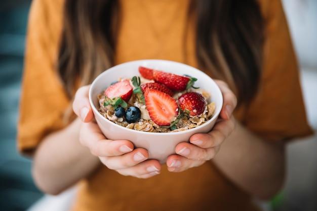 Женщина, держащая овсянку с ягодами в миске Бесплатные Фотографии