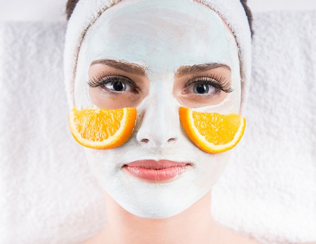 Woman holding orange slices and mask on the face. Premium Photo