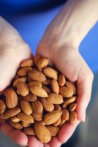 Woman holding organic almond nuts in hands Premium Photo
