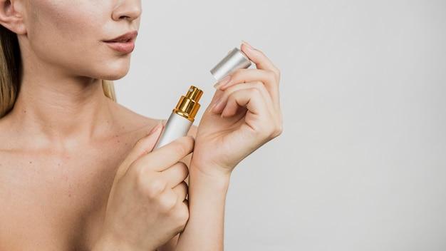 Woman holding perfume vaporizer Free Photo
