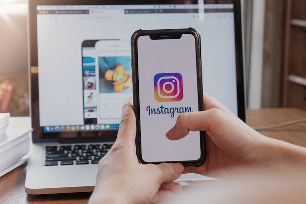 Woman holding phone with instagram application on the screen Premium Photo
