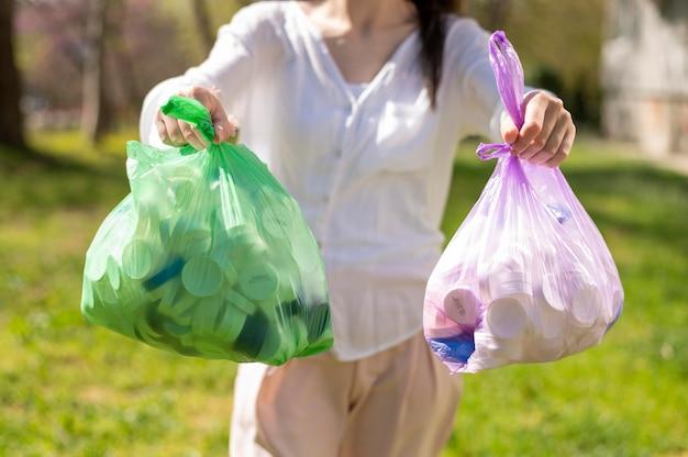 ゴミとビニール袋を保持している女性 無料写真
