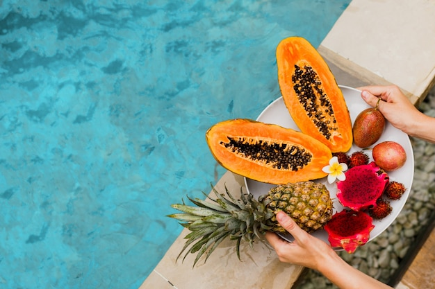 Woman holding plate of tasty tropical exotic fruits on the edge of pool, breakfast at luxury hotel. Free Photo