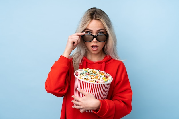 Woman holding popcorns over isolated wall Premium Photo