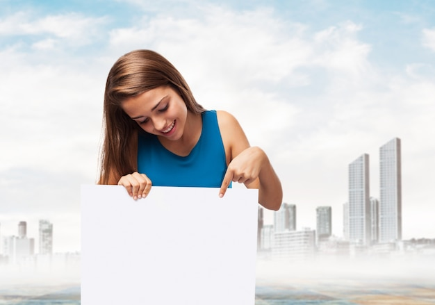 Woman holding a poster with a town background Free Photo