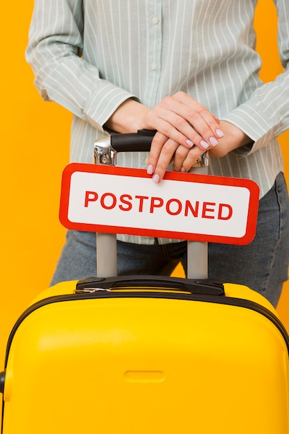 Woman holding a postponed card close-up Free Photo