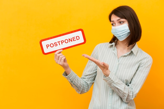 Woman holding a postponed sign on yellow background Premium Photo