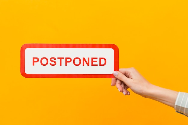 Woman holding a postponed sign Premium Photo