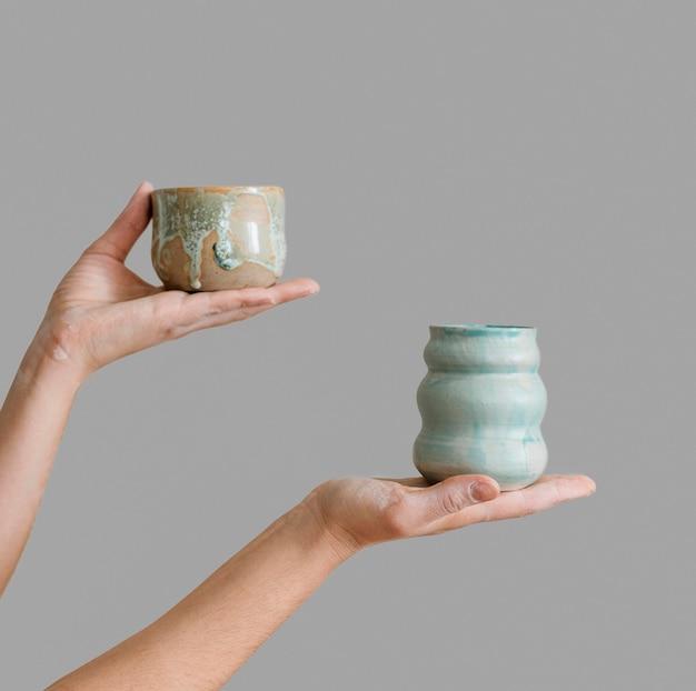 Donna che mantiene pezzi di ceramica realizzati da lei stessa Foto Gratuite