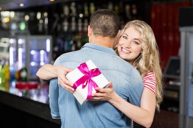 Женщина держит подарок во время обнимать парня Premium Фотографии