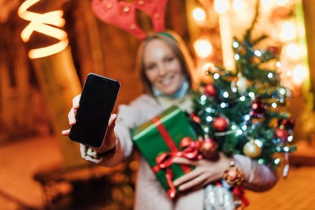 Женщина держит подарки, елку и телефон с черным экраном Premium Фотографии