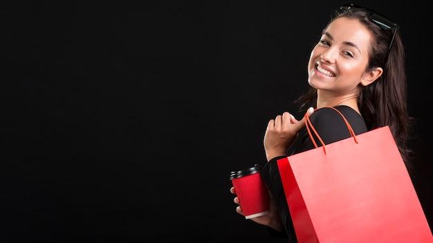 赤い大きな買い物袋のコピースペースを保持している女性 Premium写真