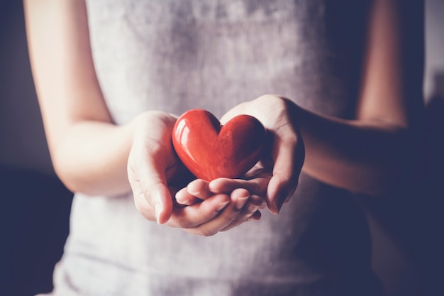 Woman holding red heart, health insurance, donation charity concept Premium Photo