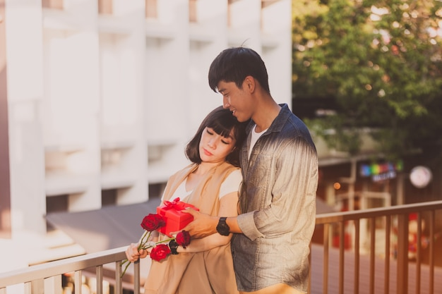 Woman holding roses while her boyfriend gives her a gift box Free Photo