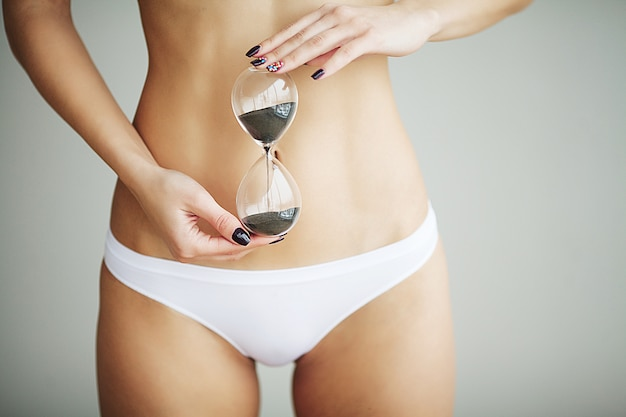 Woman holding sand clock over her stomach. health hygiene sexual education concept Premium Photo
