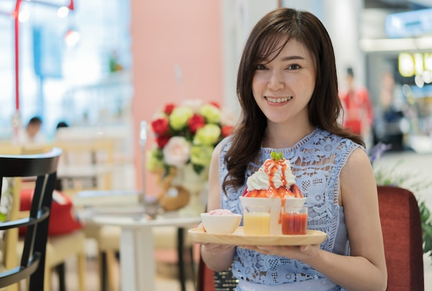 Woman holding shaved ice or strawberry bingsu fresh milk Premium Photo