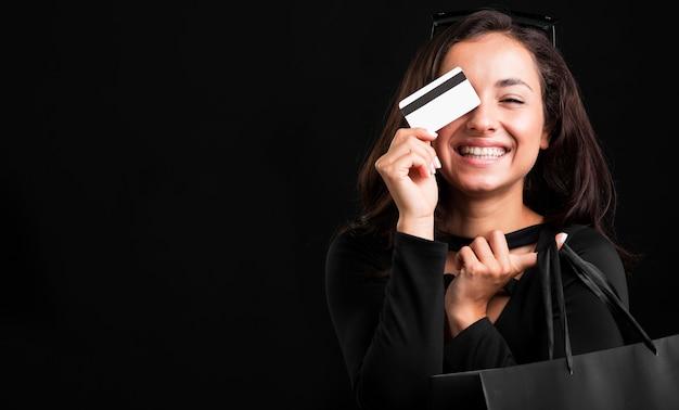 ショッピングバッグとクレジットカードを持っている女性 Premium写真