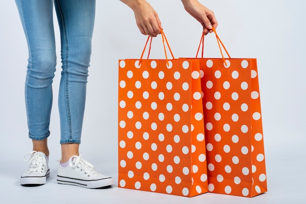 Woman holding shopping bags mock-up near legs Free Photo