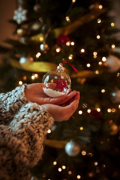 Женщина, держащая маленькую безделушку в руке Premium Фотографии